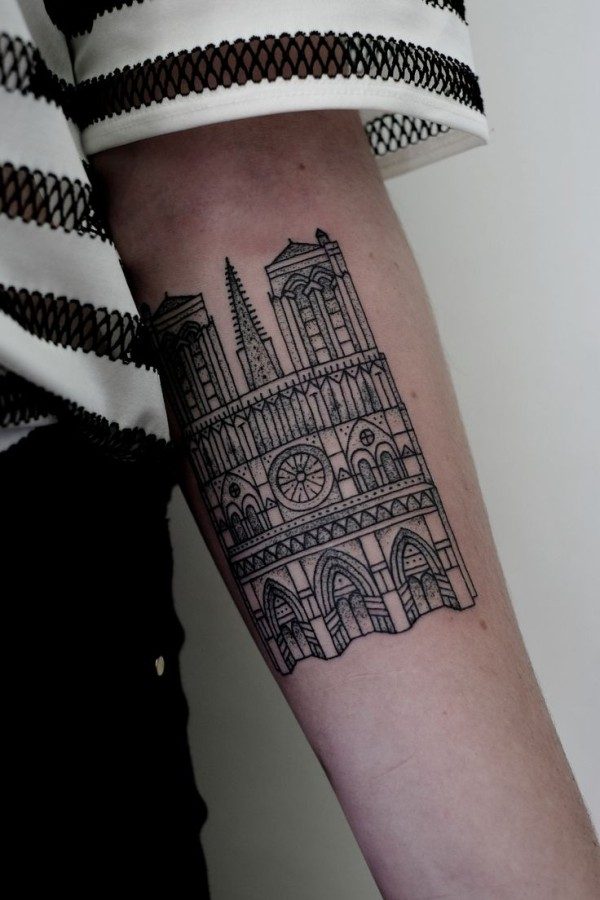 Little simple black ink tattoo on forearm of old cathedral