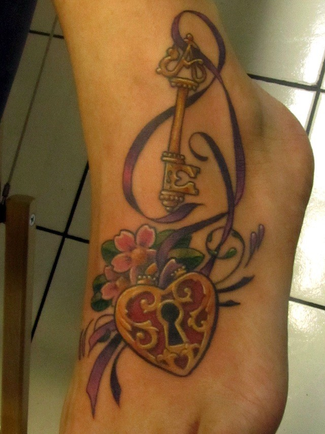 Lock and key with ribbon foot tattoo
