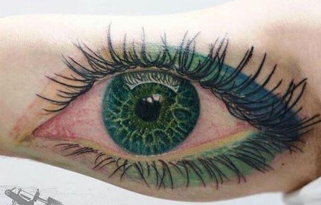 bello occhio verde con trucco verde tatuaggio su braccio da cris gherman