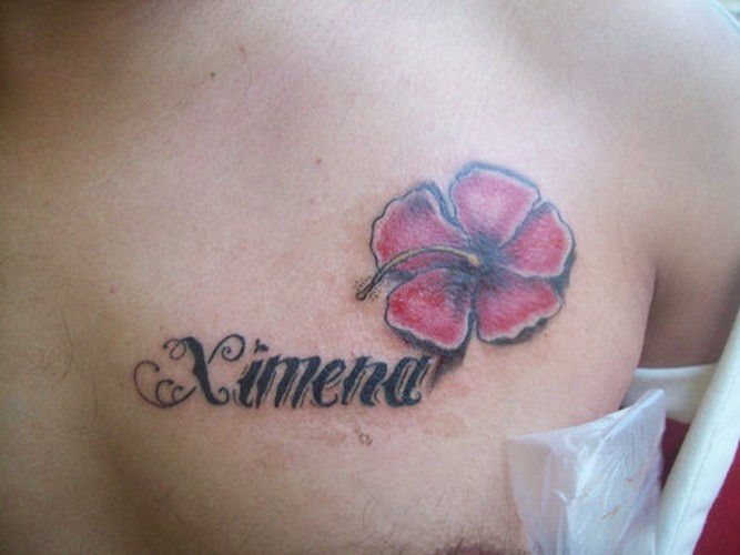 Lovely pink hawaiian flower with quote tattoo on chest