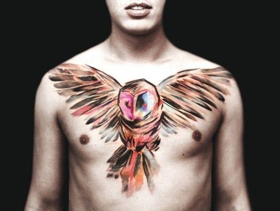 Tatuaggio grande sul petto il gufo colorato sbatte le ali