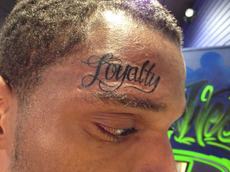Loyalty lettering face tattoo