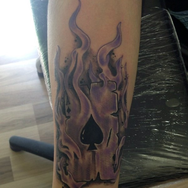 Magnificent black ink spades playing card in flames tattoo on arm