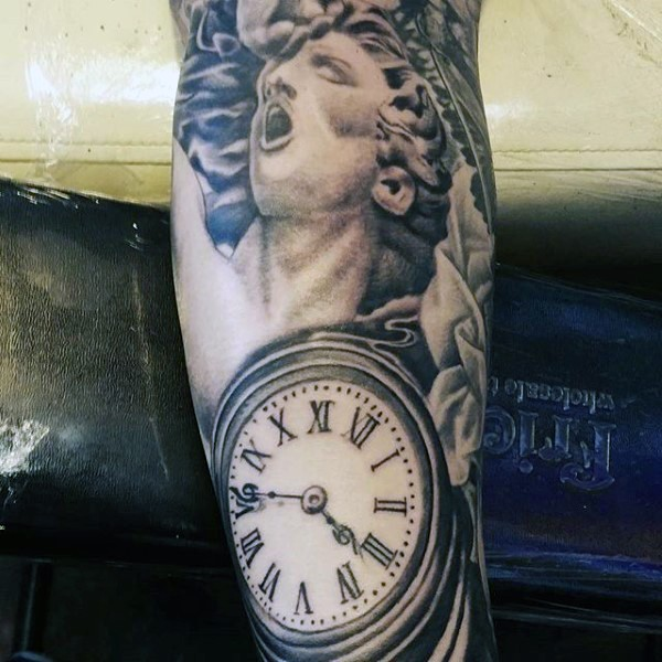 Magnificent black ink statue tattoo on forearm with old clock