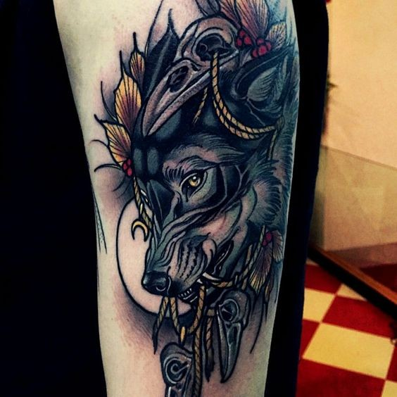 Magnificent colored big wolf face tattoo on forearm stylized with crow skulls