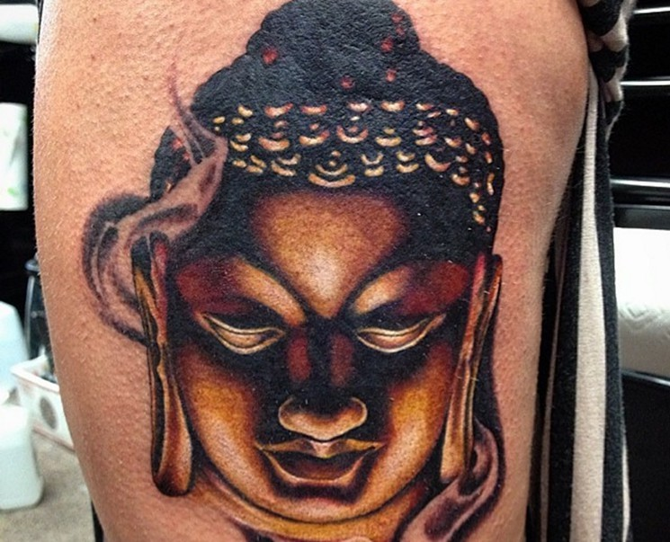 Magnificent colored detailed Hinduism Buddha&quots portrait thigh tattoo with smoke