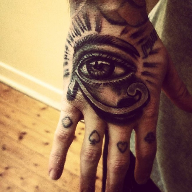 Magnificent Egyptian ancient symbol the Eye of Horus tattoo on hand with card suit on fingers