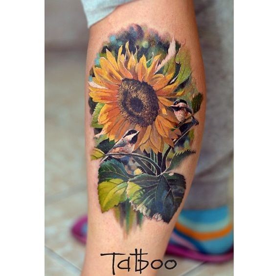 Magnificent multicolored lifelike sunflower and tiny birds tattoo on man&quots forearm in realism style