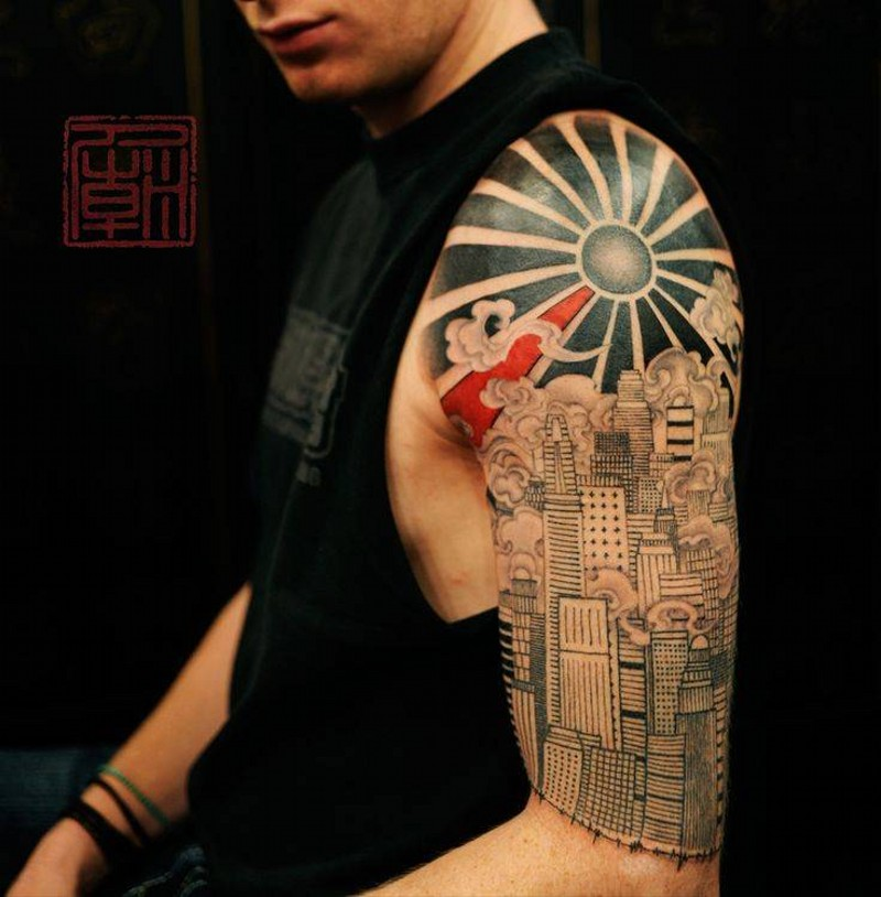 Magnificent painted detailed black ink sun tattoo on shoulder combined with steamy city