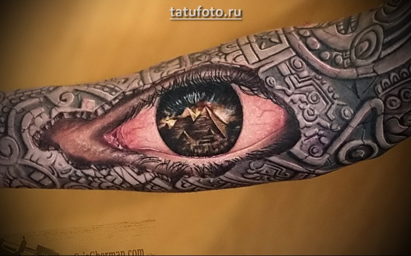 Magnificent very detailed colorful eye tattoo on forearm stylized with Egypt pyramids and ornaments