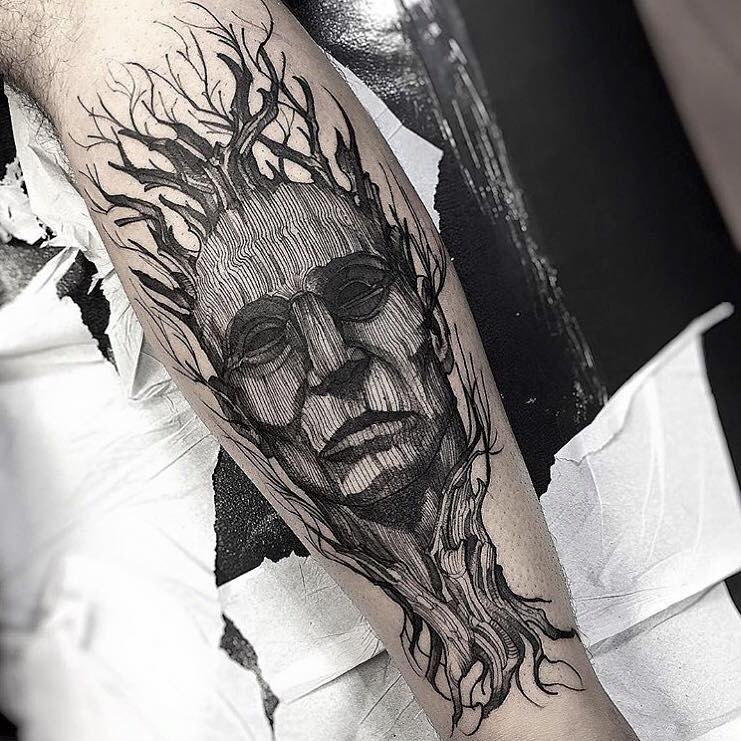 Man&quots portrait designed with tree elements forearm tattoo in surrealism engraving style