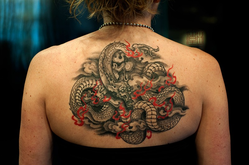 Marvelous black and white upper back tattoo of dragon with flames