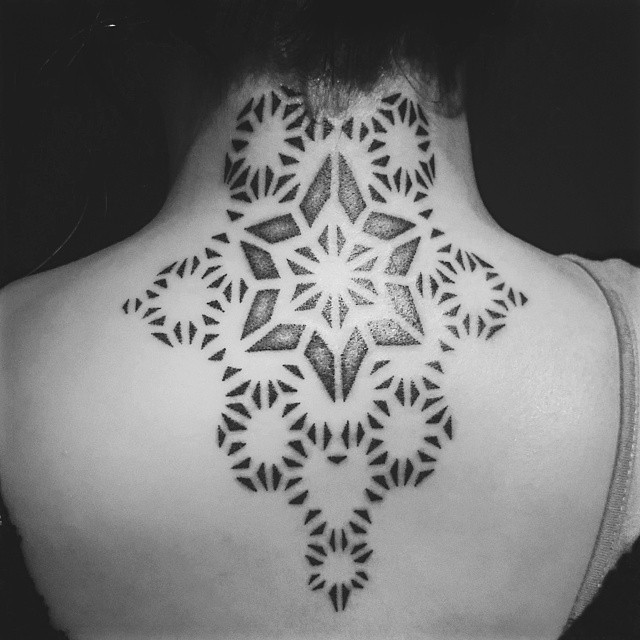 Marvelous black ink ornamental tattoo on upper back and neck