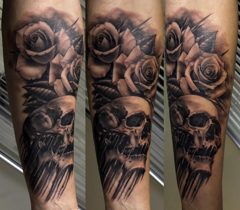 Marvelous black ink rose flowers tattoo on forearm combined with human skull