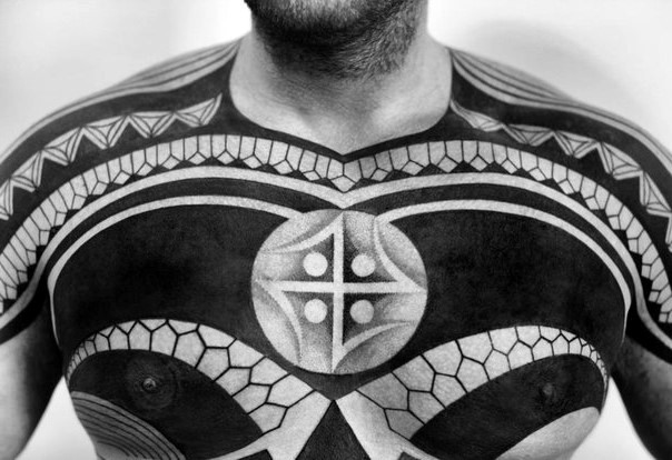 Massive black and white tribal style tattoo with mystic symbol on chest and shoulder
