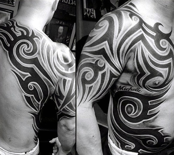 Massive black and white tribal tattoo with lettering on chest, shoulder and side
