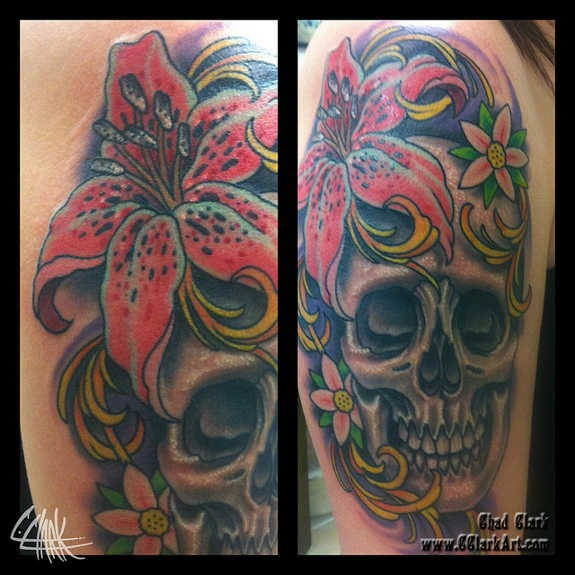 Massive old school colored human skull tattoo on shoulder combined with beautiful flowers