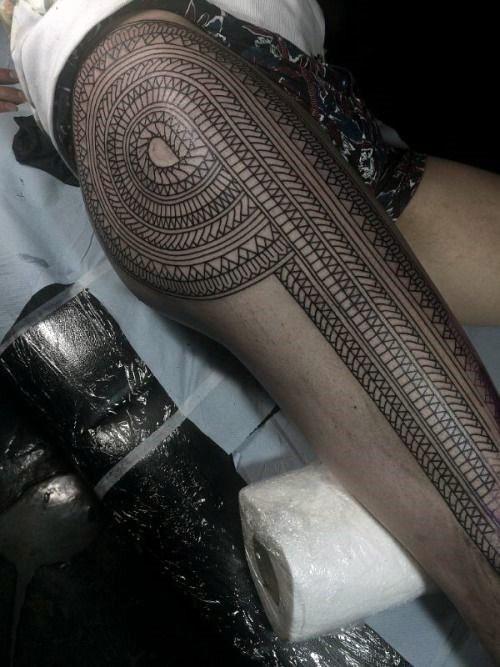 Massive very detailed black ink tribal tattoo on whole leg
