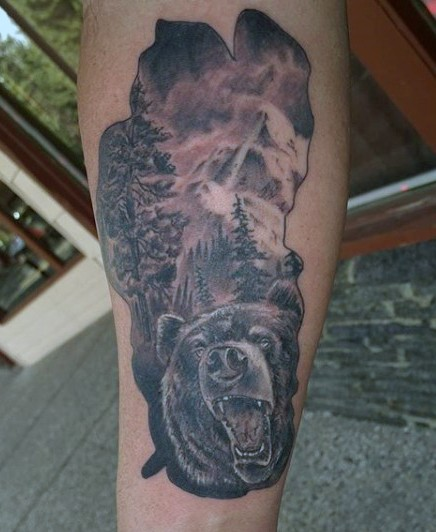 Massive wild life themed black and white bear in mountain forest tattoo on arm