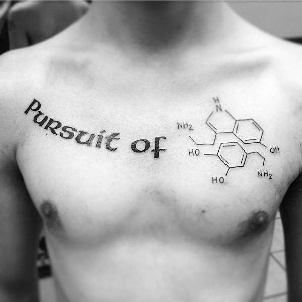 Meaningful dark black ink lettering Pursuit of tattoo on man&quots chest with chemical formula drawing