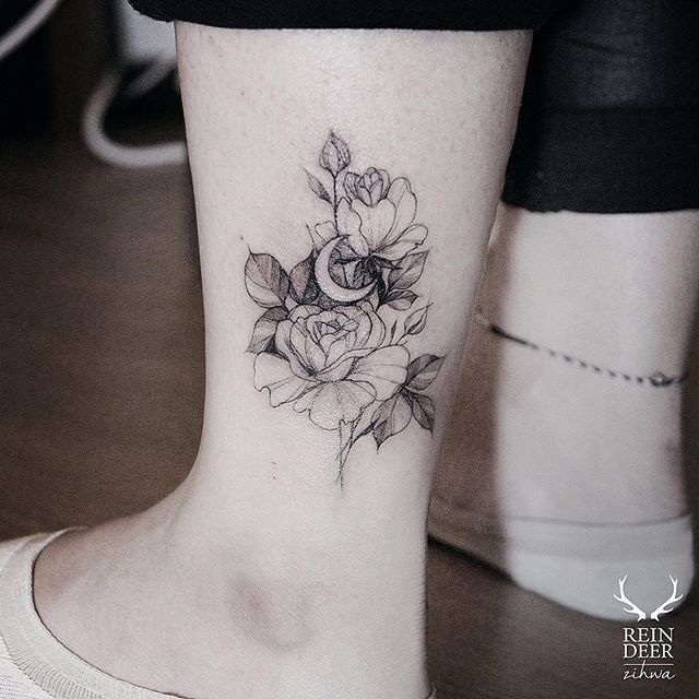 Medium size blackwork style ankle tattoo by Zihwa of flowers with moon