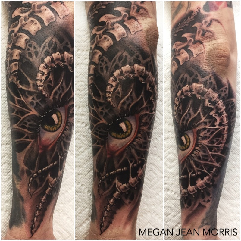 Medium size colored arm tattoo of mystical looking eye with bones