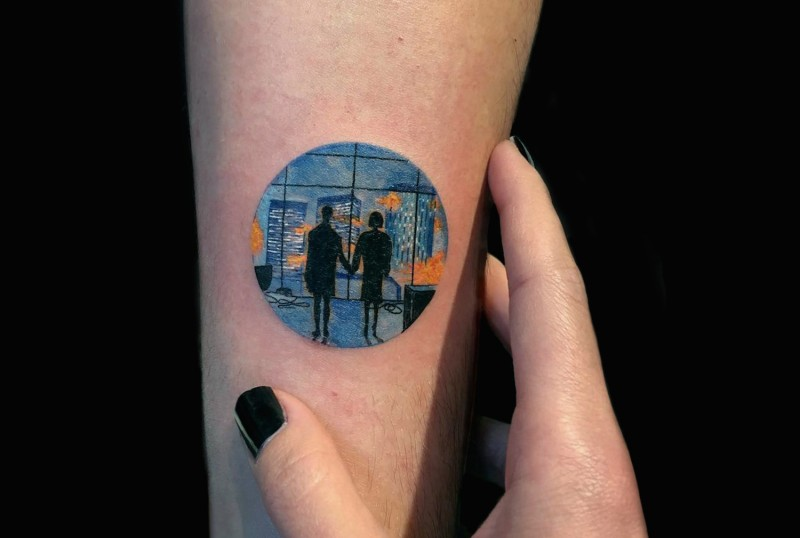 Medium size colored circle shaped tattoo stylized with couple in night city