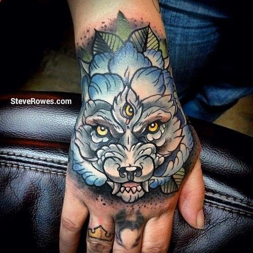 Medium size colored mystical wolf with three eyes tattoo on hand stylized with leaves
