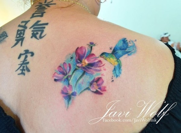 Medium size watercolor style beautiful looking shoulder tattoo of hummingbird and flowers