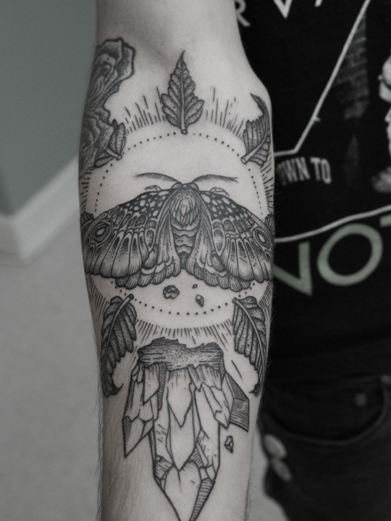 Men&quots black-and-white moth in sun with leaves tattoo on forearm