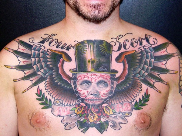 Mexican native colored man portrait tattoo on chest stylized with wings and lettering