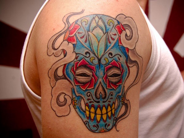 Mexican native multicolored smiling skull tattoo on shoulder zone
