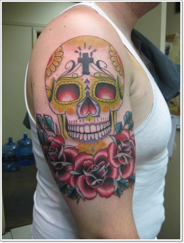 Tatuaje en el brazo,  calavera de azucar sonriente y rosas rojas