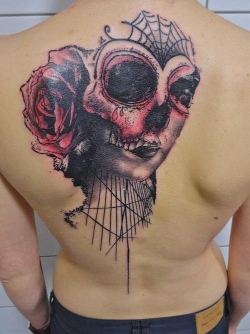 Mexican style colored skull with flower tattoo on upper back