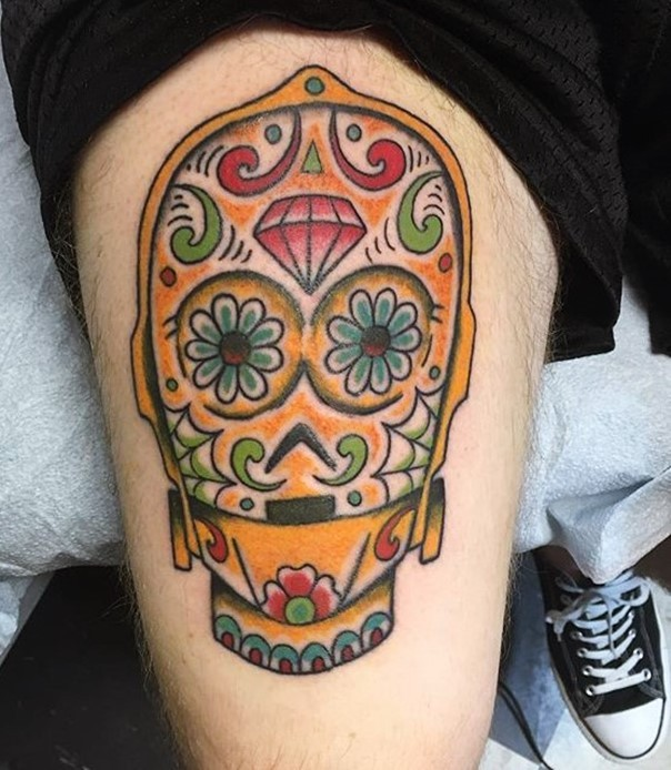 Mexican style deigned and colored big C3PO head tattoo on thigh