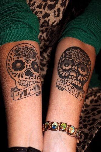 stile Messicano differente colorato piccolo cranio con lettere e fiori tatuaggio su braccio
