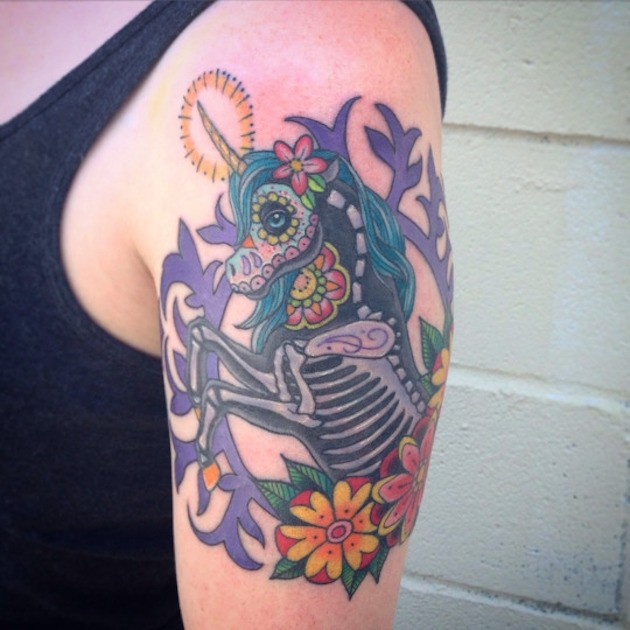 Mexican style unicorn with skeleton elements framed shoulder colored tattoo with flowers