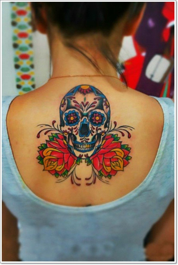 Mexican sugar skull tattoo with red flowers tattoo on back