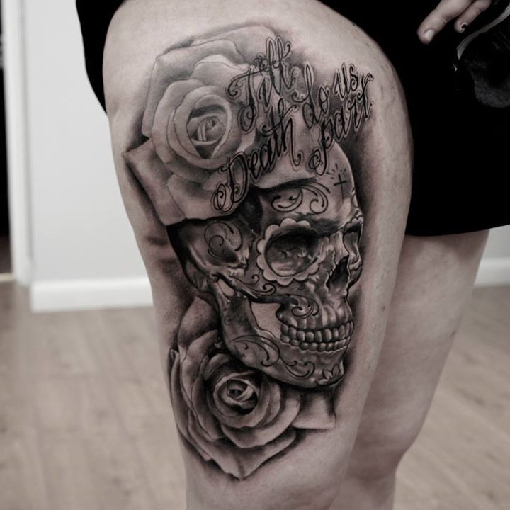 Mexican traditional black and white thigh tattoo of human skull stylized with flowers and lettering