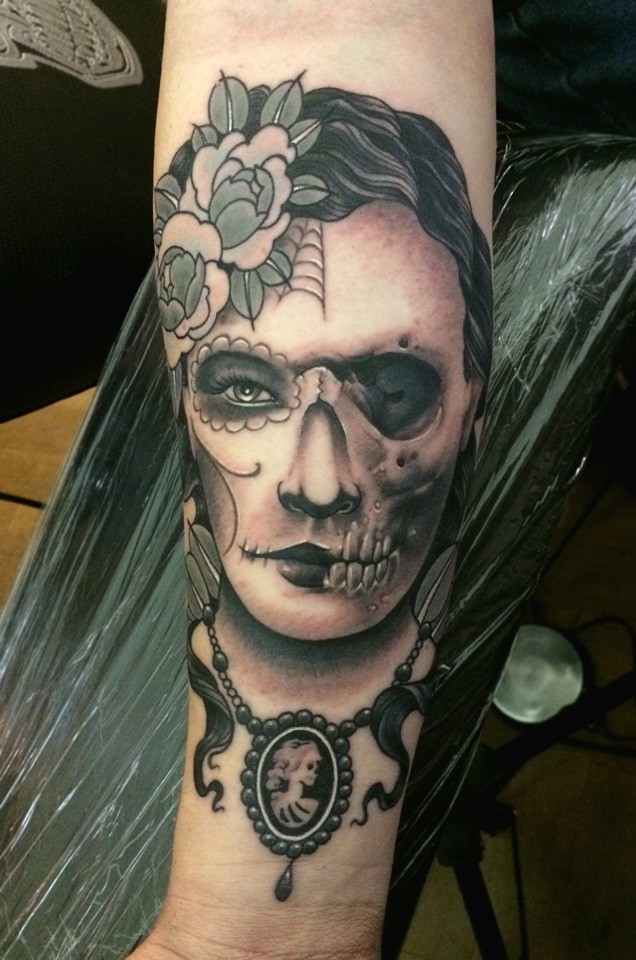 Mexican traditional colored forearm tattoo of half woman half skull portrait
