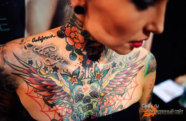 Mexican traditional colored skull with wings tattoo on chest stylized with lettering and butterfly