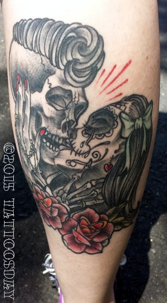 Mexican traditional style colored tattoo of kissing skeleton couple with flowers