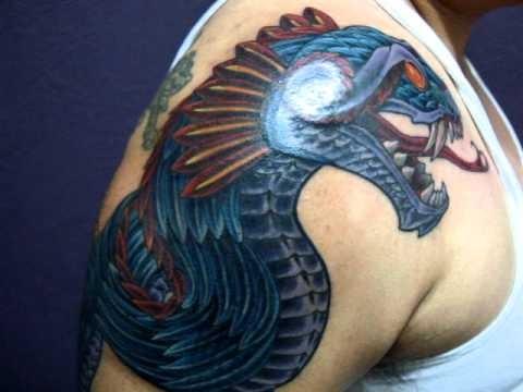 Modern illustrative style colored shoulder tattoo of evil fantasy dragon