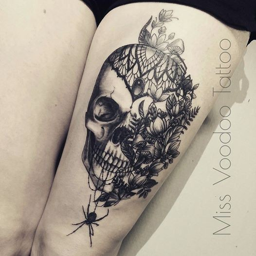 Modern looking black ink thigh tattoo of big human skull with flowers and spider by Caro Voodoo