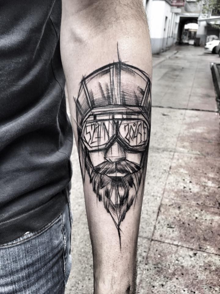 Modern style black ink painted by Inez Janiak forearm tattoo of man with glasses and helmet