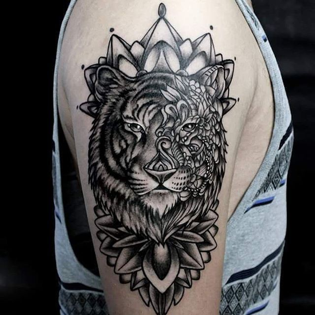 Modern style black ink shoulder tattoo of tiger stylized with various flowers