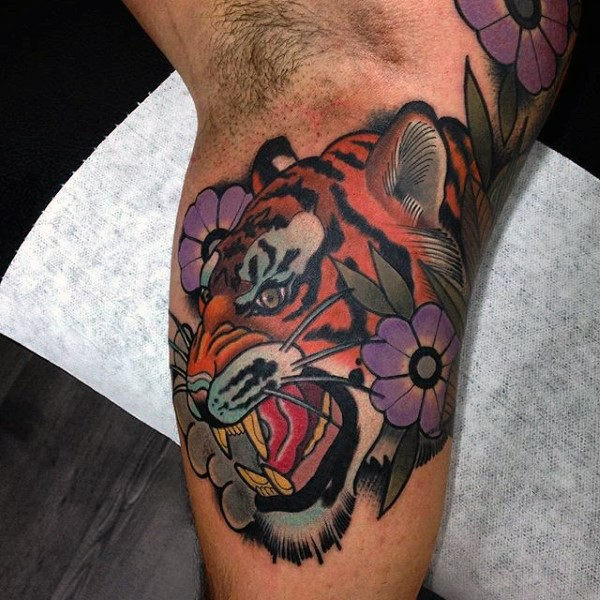 Modern style colored biceps tattoo of roaring tiger with flowers