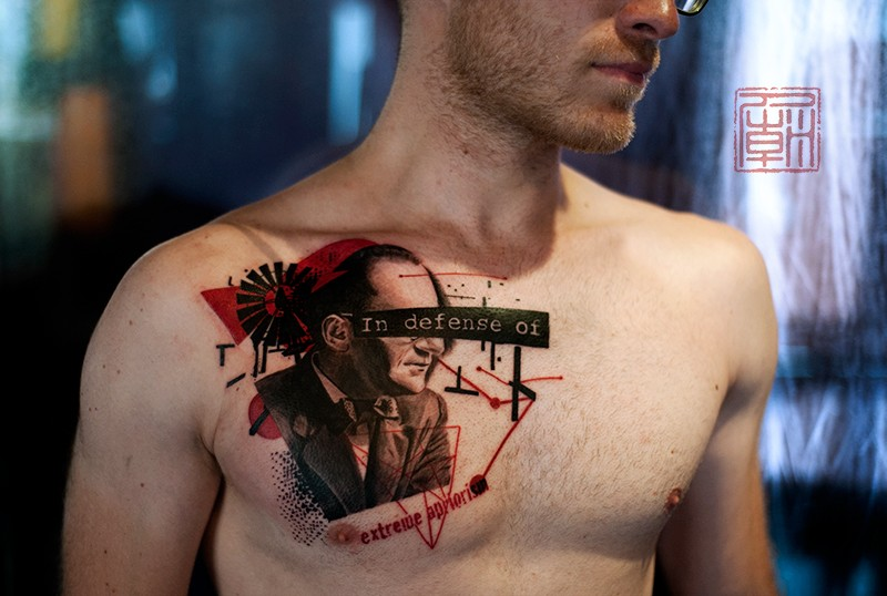 Modern style colored man portrait tattoo on chest combined with lettering
