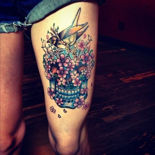 Modern style colored skull tattoo on thigh with flowers and beautiful bird