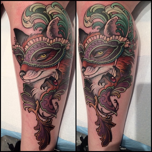 Modern style multicolored fox with mask tattoo on leg stylized with feather